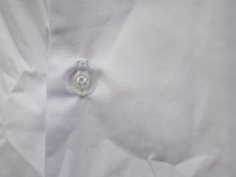 Semi кнопка прозрачной пластмассы на белой рубашке хлопка стоковые изображения