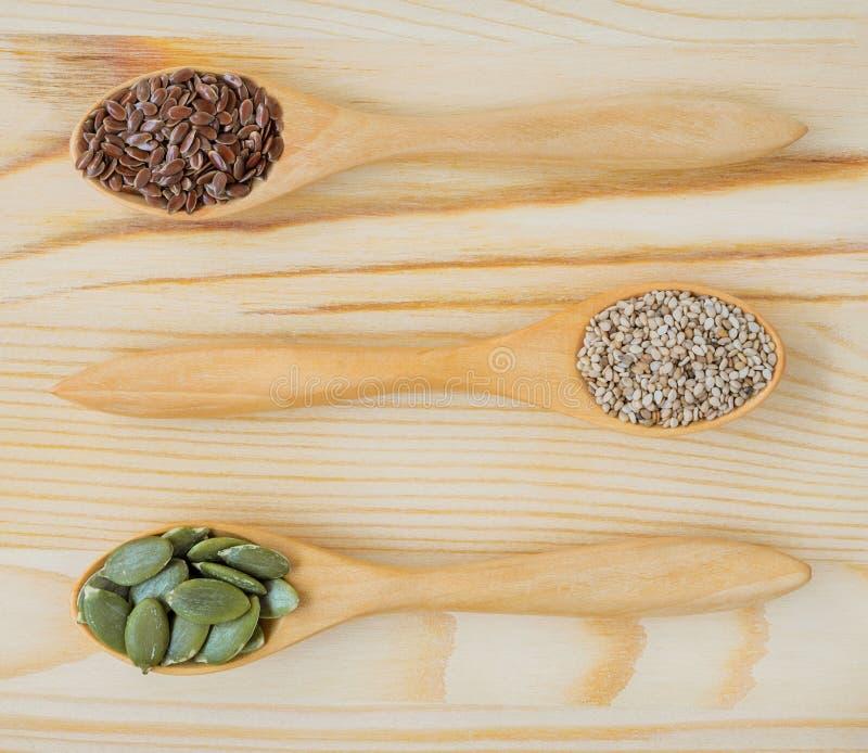 Semi asciutti del lino, del sesamo e di zucca in cucchiaio di legno fotografia stock libera da diritti
