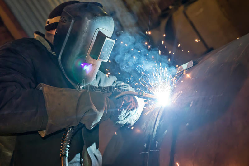 Semi-automatic welding with sparks and smoke. Welding large diameter pipe in workshop conditions by the method of semi-automatic welding in shielding gases royalty free stock images