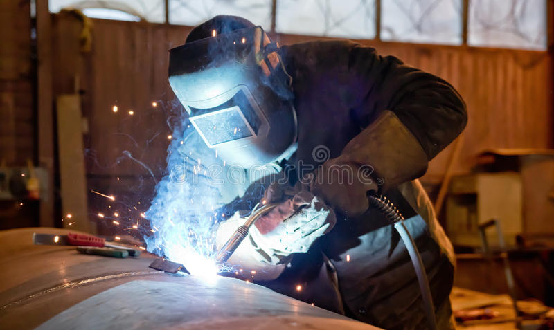 Semi-automatic welding with sparks and smoke. Welding large diameter pipe in workshop conditions by the method of semi-automatic welding in shielding gases stock photos