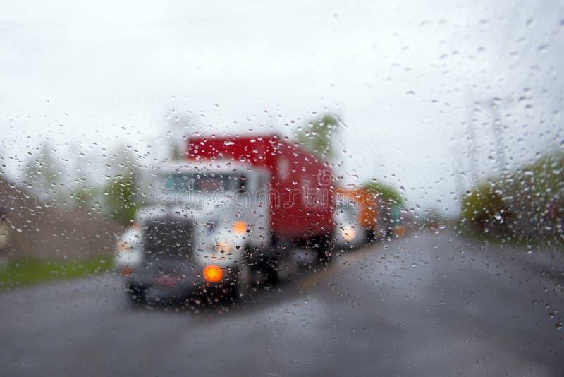 Semi borroso convoy de camión en gotas de lluvia y linterna en el camino imagen de archivo libre de regalías