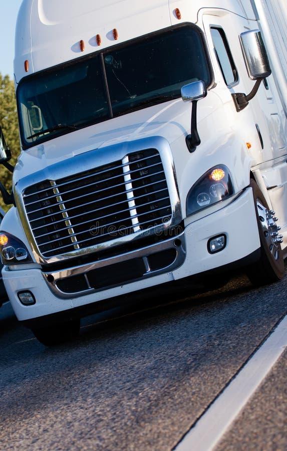 Semi camión moderno blanco con el remolque que conduce con el cargo en marke imágenes de archivo libres de regalías
