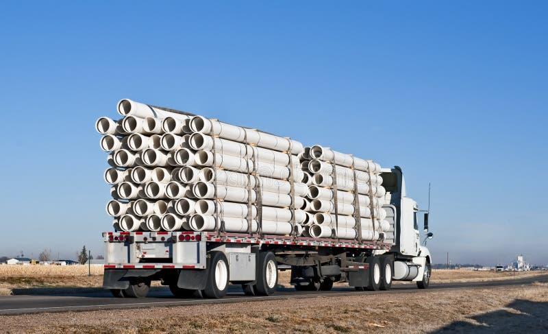 Semi-camion avec un chargement de pipe en plastique image libre de droits