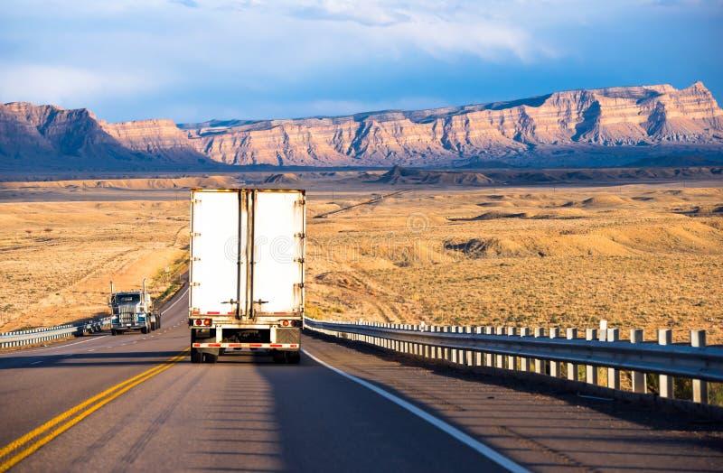 Semi camiones con los remolques que llevan el cargo en la carretera imagen de archivo libre de regalías
