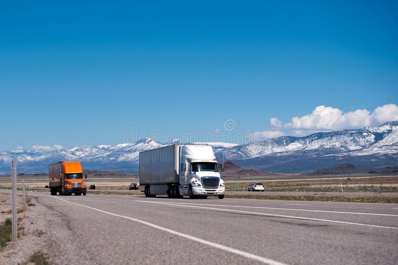 Semi camiones y remolques blancos y anaranjados en alta manera fotografía de archivo