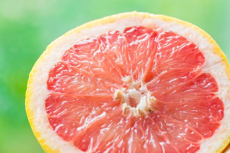 Semi Circle Slice of Ripe Juicy Red Grapefruit on Green Foliage Nature Background. Vitamins Healthy Diet Summer Detox Vegan. Superfoods Concept. Poster Banner royalty free stock photos