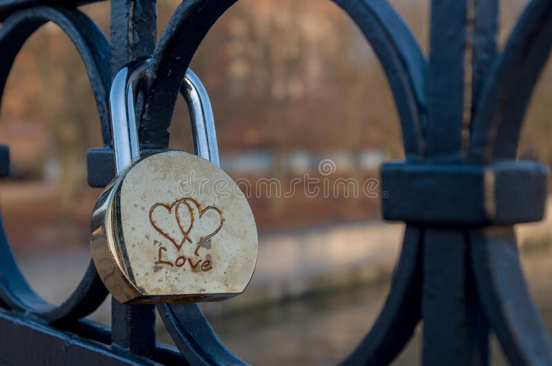 Semi-circular shiny golden-silver padlock engraved with two woven hearts fixed on round elements of bridge fence. Semi-circular shiny golden-silver padlock with stock images