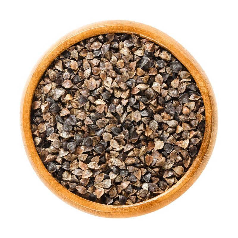 Semi comuni del grano saraceno con i gusci in ciotola di legno fotografie stock