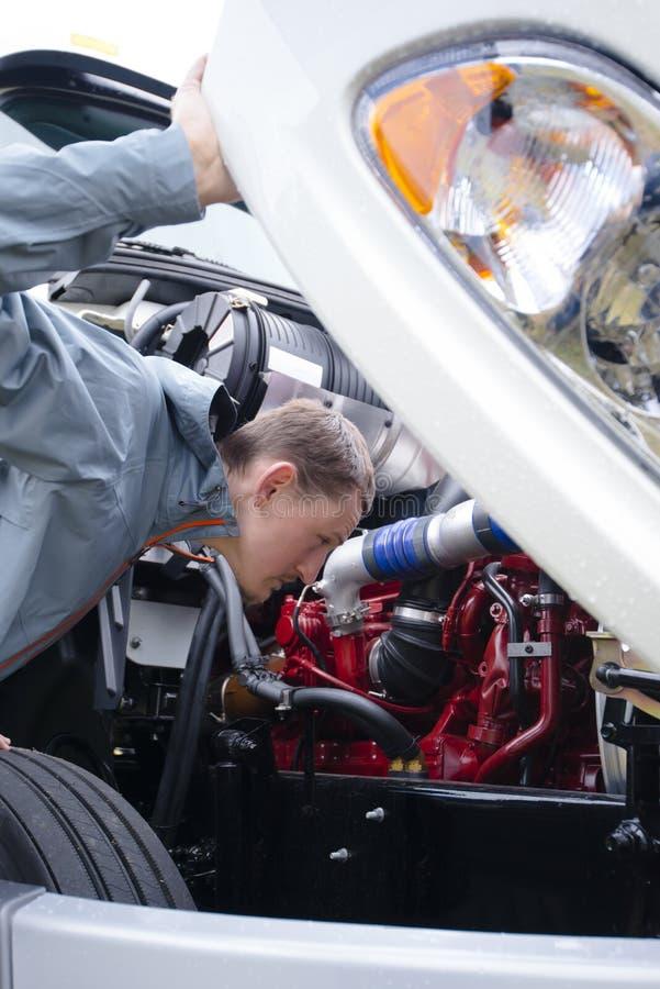 Semi de vrachtwagenmotor die van de vrachtwagenchauffeurcontrole binnenkap kijken stock foto's
