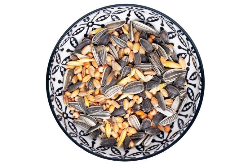 Semi dell'uccello Primo piano di una ciotola decorativa con i semi di girasole neri ed altri seme e dadi per l'alimentazione degl immagine stock
