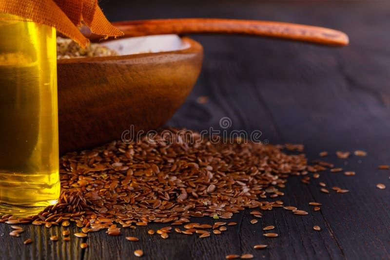 Semi di lino di Brown in cucchiaio e olio di semi di lino in bottiglia di vetro su fondo di legno bianco L'olio del lino è ricco  fotografia stock libera da diritti