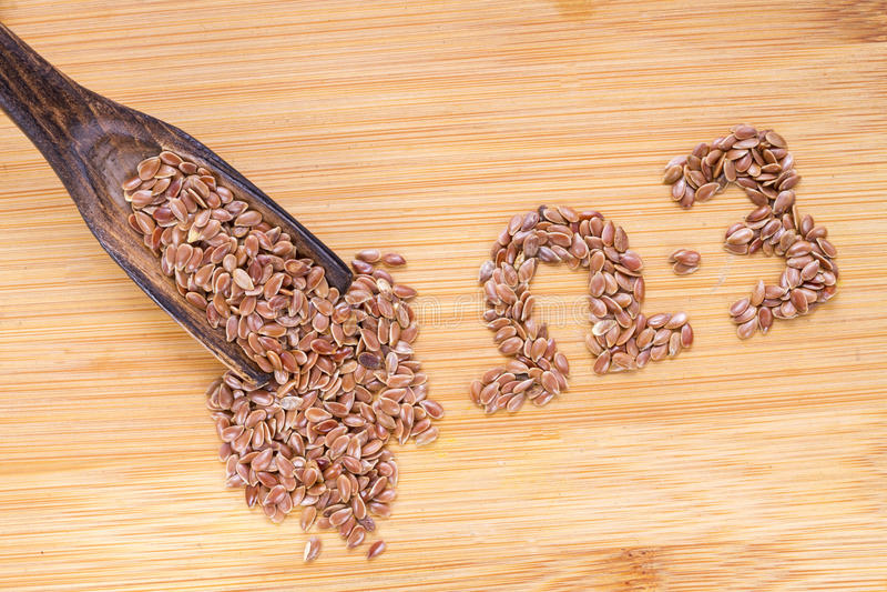 Semi di lino in ciotola e cucchiaio di legno immagini stock libere da diritti