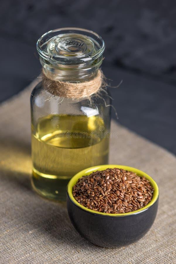 Semi di lino in un olio biondo del seme di lino e del mucchio in una bottiglia di vetro sulla tavola Dieta sana con Omega 3 acidi fotografia stock