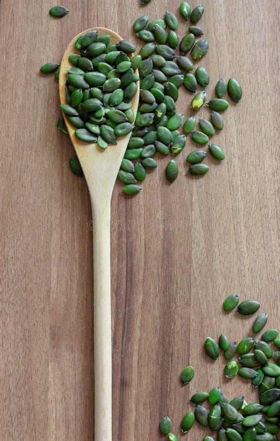 Semi di zucca sul cucchiaio di legno fotografia stock libera da diritti