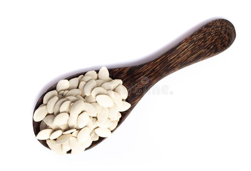 Semi di zucca sul cucchiaio di legno su fondo bianco fotografia stock libera da diritti