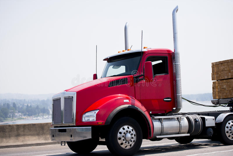 Semi el camión moderno rojo con el taxi del día y el remolque de la cama plana llevan el lu imágenes de archivo libres de regalías