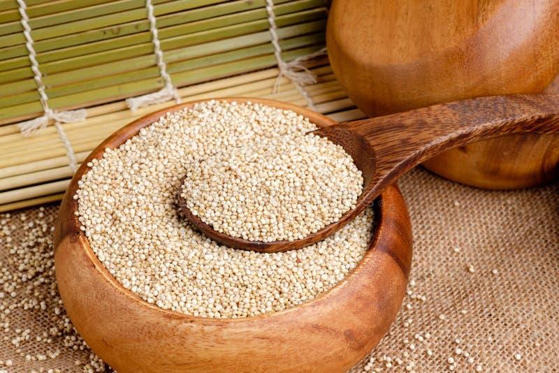 Semi organici della quinoa in ciotola di legno immagine stock