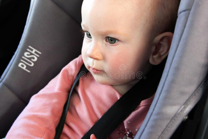 A semi profile portrait of a baby in a car seat stock photo