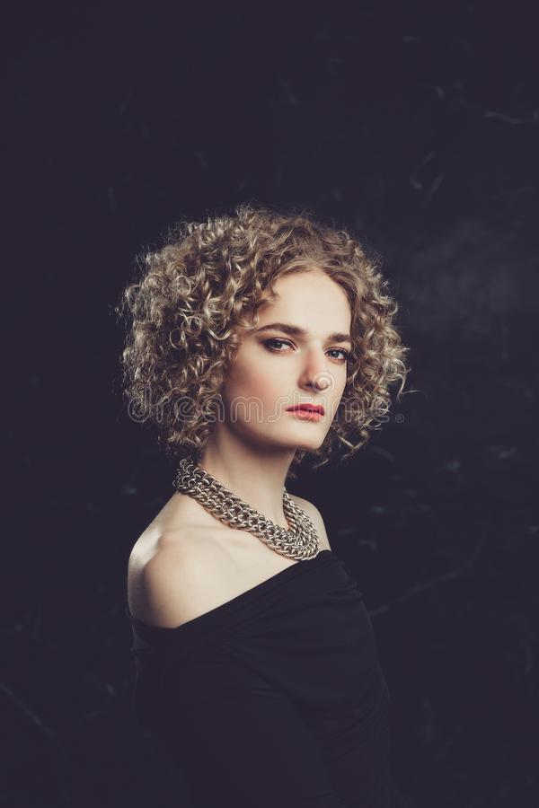 A semi-profile portrait of transgender guy model with blue eyes and blond hair in the image of a girl with chain around neck royalty free stock photos