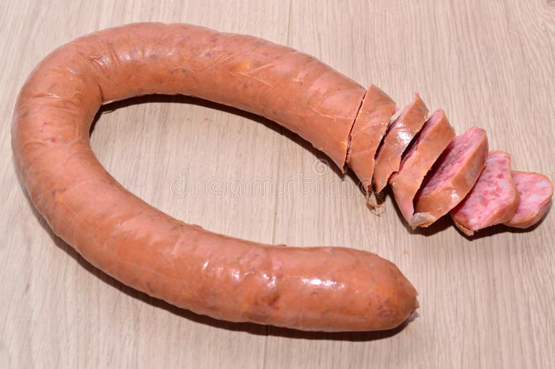 Semi smoked sausage. Semi smoked sausage on a wooden table stock images