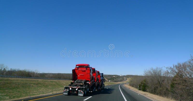Semi tractor que acarrea semi los camiones, rojo, en la carretera fotos de archivo libres de regalías