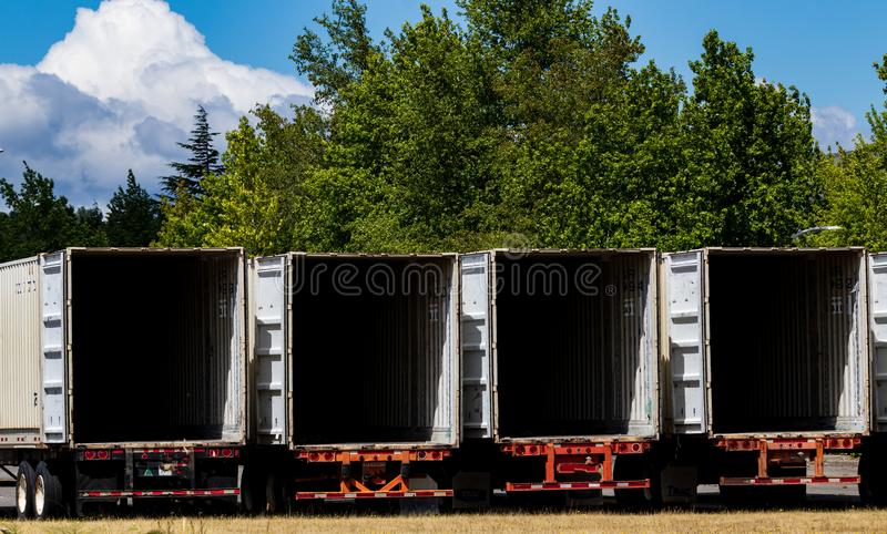 Semi tractor trailers empty and open parked in a lot with trees royalty free stock photos
