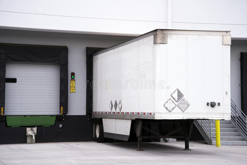 Semi trailer for big rig semi truck loading commercial cargo at warehouse dock with thermally insulated gate. Semi trailer for freight in American logistic stock photography