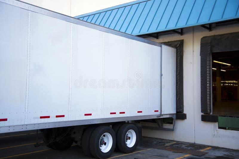Semi Trailer Unloading Cargo In Dock Warehouse With Door