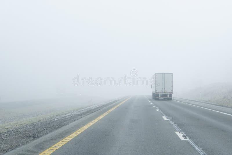 Semi-Truck Drives Into Dense Fog royalty free stock photo