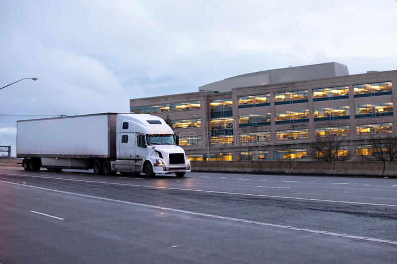 Semi truck with dry van trailer on evening road. White modern semi truck with a dry van trailer moving on evening highway with turn on headlights and reflection royalty free stock photos