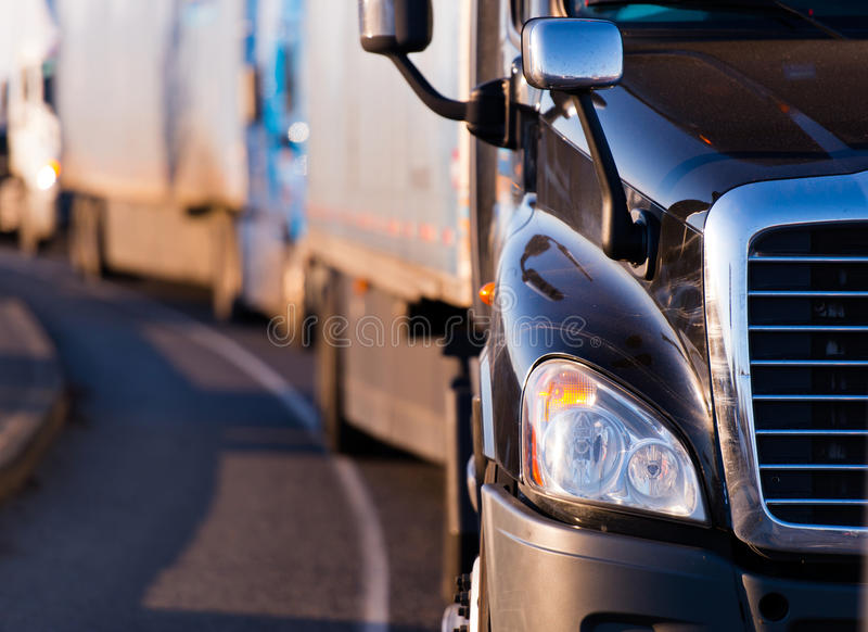 Semi truck in fronf of convoy. Details of dark semi truck on the road on blured truck and trailer background royalty free stock photos