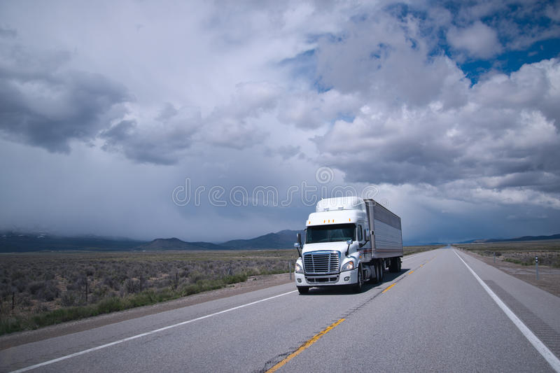 Semi truck with reefer trailer on flat long Arizona road. Single stylish professional commercial white big rig semi truck with refrigerated trailer carry cargo royalty free stock images