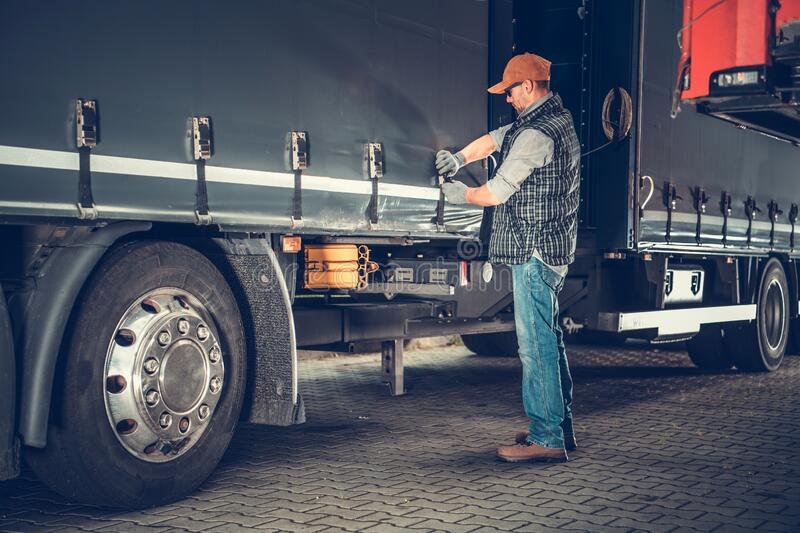Semi Truck Safety Checkup. Caucasian Trucker Preparing His Semi Truck Trailers For the Road. Safety Checkup. Transportation Industry royalty free stock photography