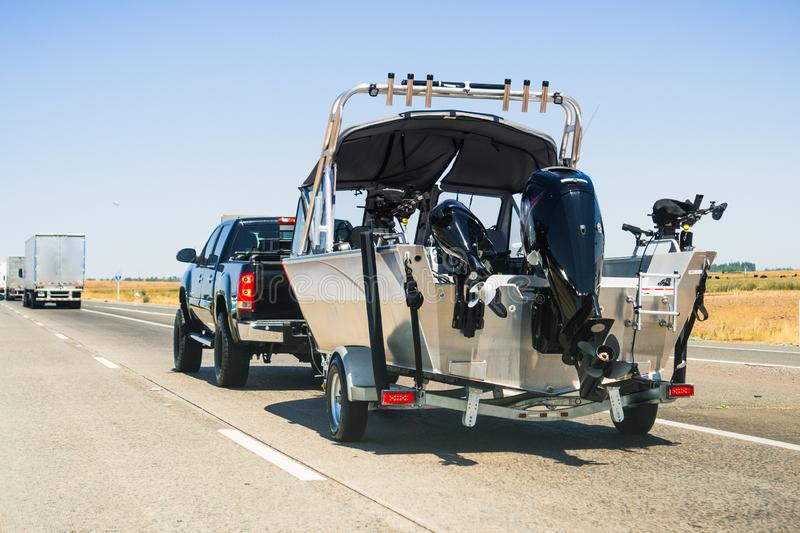 Semi-truck towing a  boat on the interstate, California stock photo