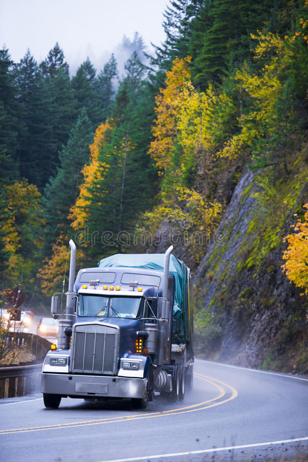 Semi truck trailer with cargo on winding autumn reoad in rain. Powerful dark blue semi truck with high chrome tailpipes with a cargo on flat bed trailer stock photos