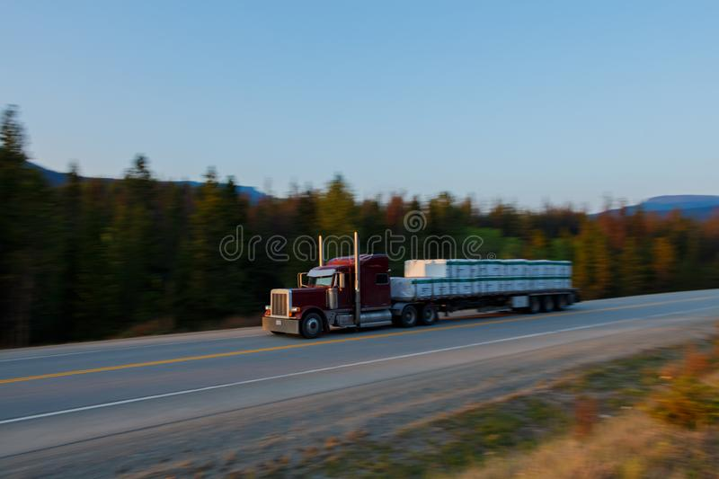 Semi truck and trailer moving fast. Motion blur stock photo
