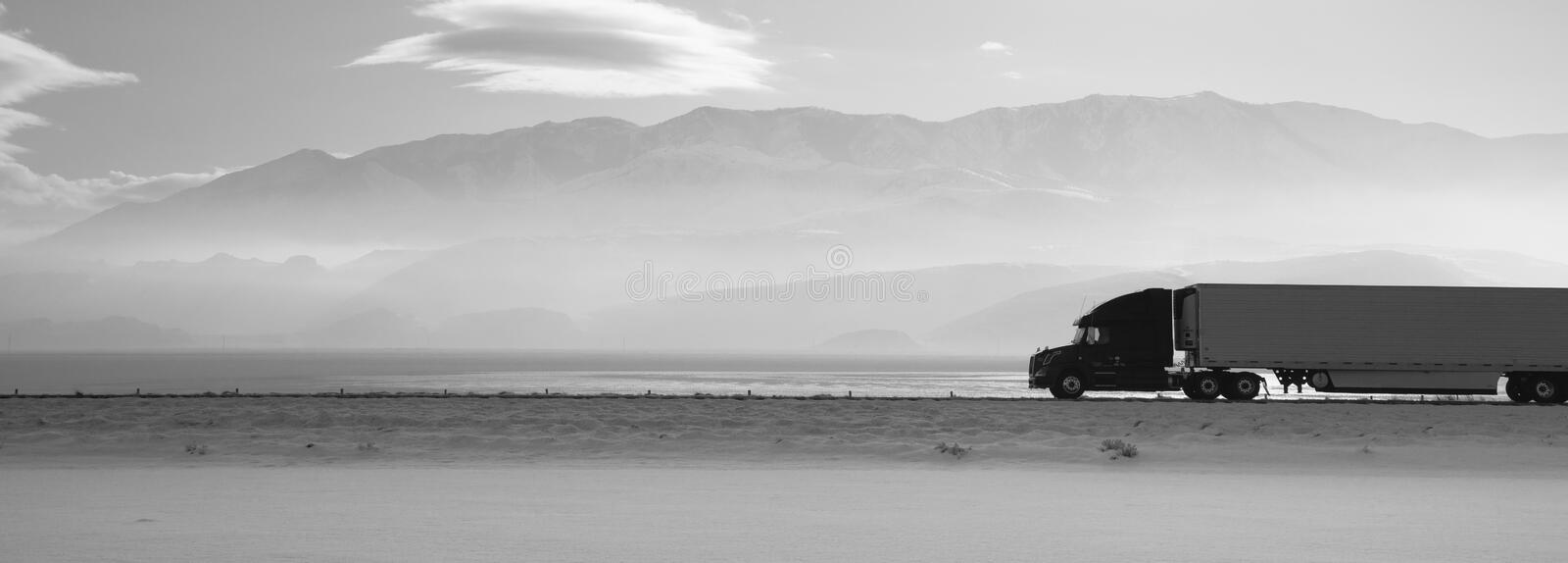 Semi Truck Travels Highway Over Salt Flats Freight Transport. Fresh snow covers the ground trucks pass late in the day on this lonely highway stock images