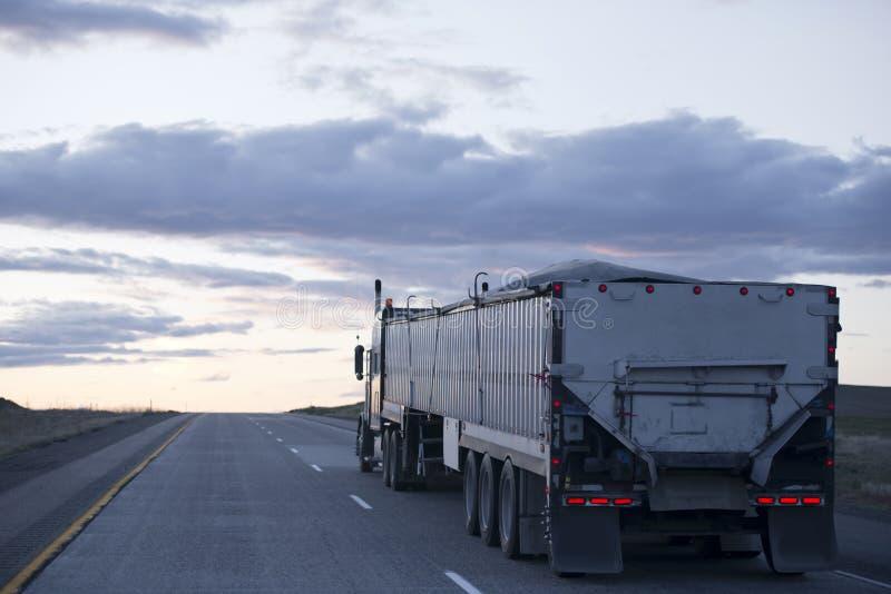 Semi vrachtwagen met lange bulkaanhangwagen op avondweg royalty-vrije stock fotografie
