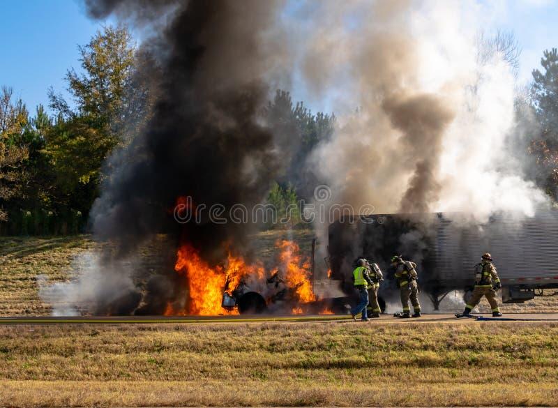 Semi vrachtwagen op brand op de weg; brandweerlieden op het werk; veiligheidsconcept royalty-vrije stock foto