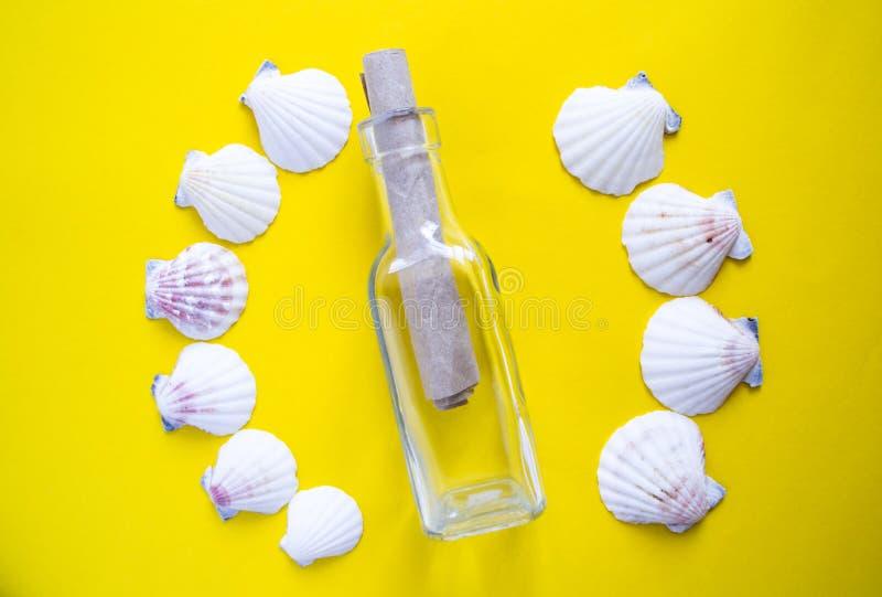 Semicerchio delle conchiglie bianche con il messaggio in una bottiglia su fondo giallo fotografia stock libera da diritti