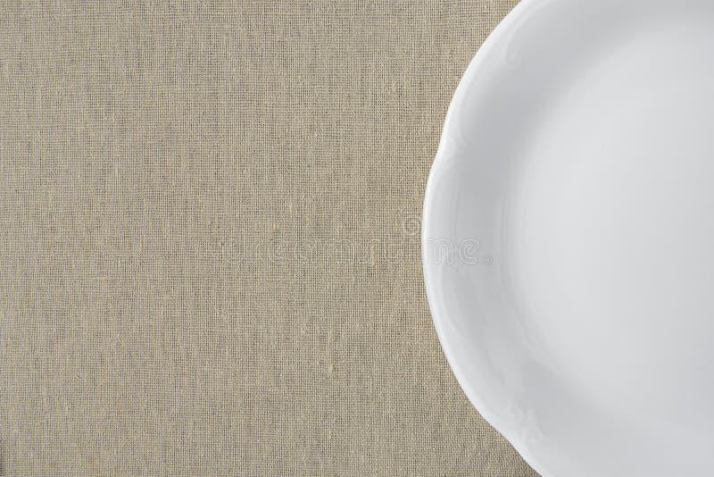Semicerchio vuoto d'annata bianco del piatto sul fondo di tela beige del tessuto Stile giapponese minimalista Modello per l'inseg fotografie stock