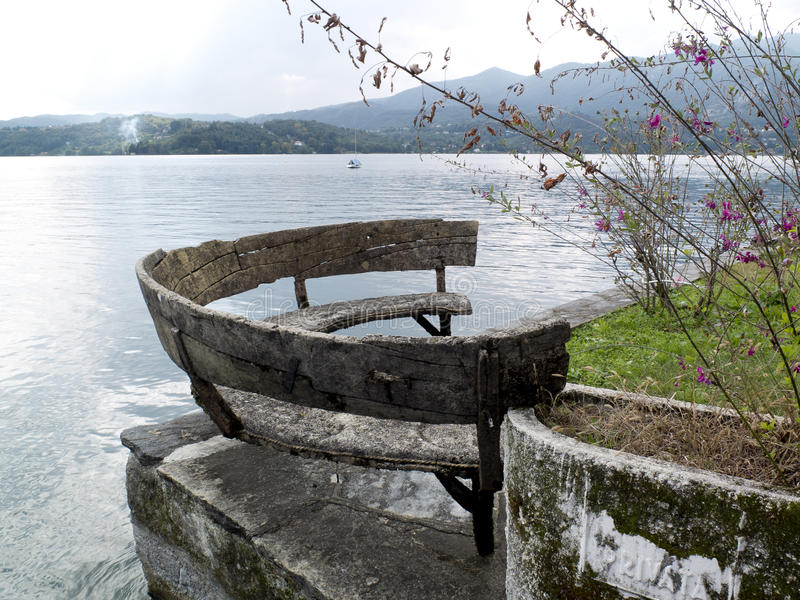Semicircular old wooden bench, Orta lake, Italy. royalty free stock photography