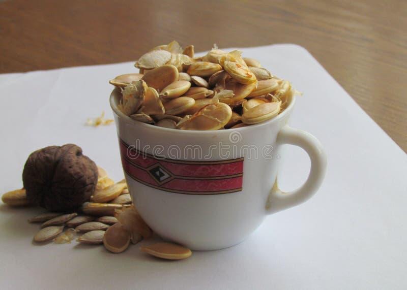Semillas de calabaza en una taza y una nuez foto de archivo
