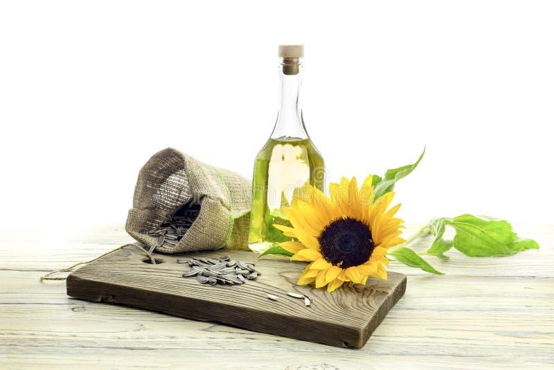 Semillas de girasol y aceite de girasol en un fondo blanco fotografía de archivo