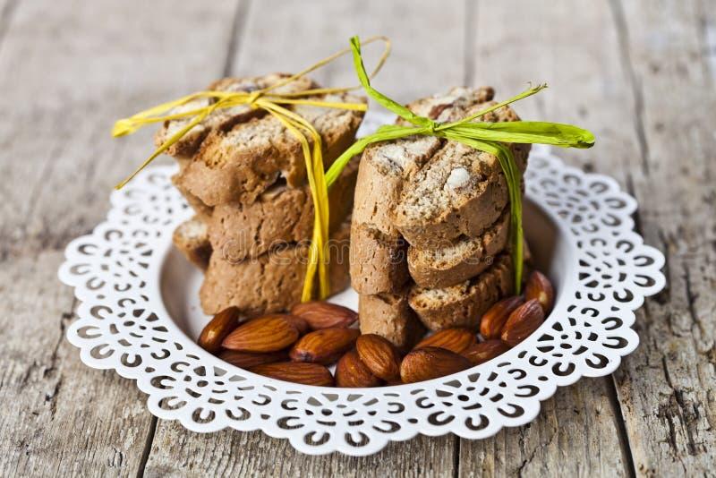 Semillas de la almendra y cantuccini italiano fresco de las galletas apilados en la placa blanca en fondo de madera ructic de la  foto de archivo libre de regalías