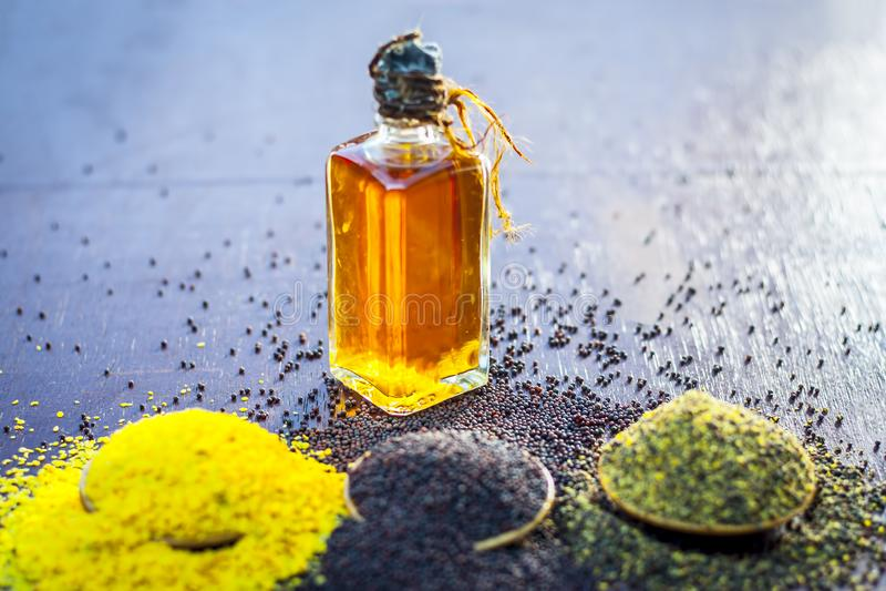 Semillas de la mostaza morena, el aceite de semilla de mostaza y semillas de mostaza machacadas en la superficie de madera marrón fotografía de archivo libre de regalías