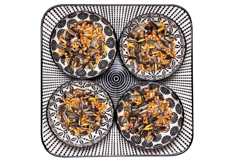 Semillas del pájaro Primer de una placa decorativa con cuatro cuencos con las semillas de girasol negras y otra semilla y nueces  imagenes de archivo