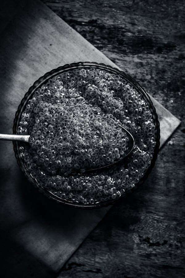 Semillas empapadas de la albahaca dulce o semillas del sabja en un bol de vidrio en superficie de madera imagen de archivo