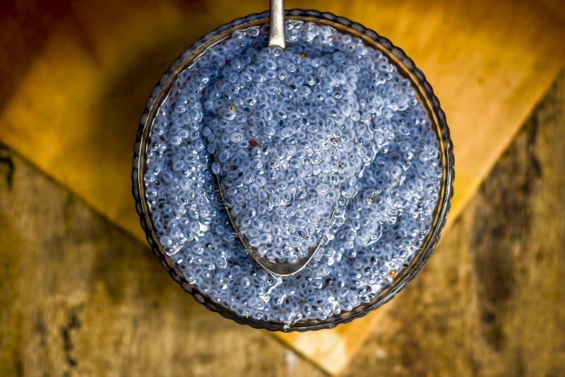Semillas empapadas de la albahaca dulce o semillas del sabja en un bol de vidrio en superficie de madera fotografía de archivo libre de regalías