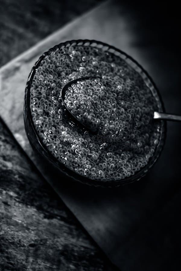 Semillas empapadas de la albahaca dulce o semillas del sabja en un bol de vidrio en superficie de madera imagenes de archivo